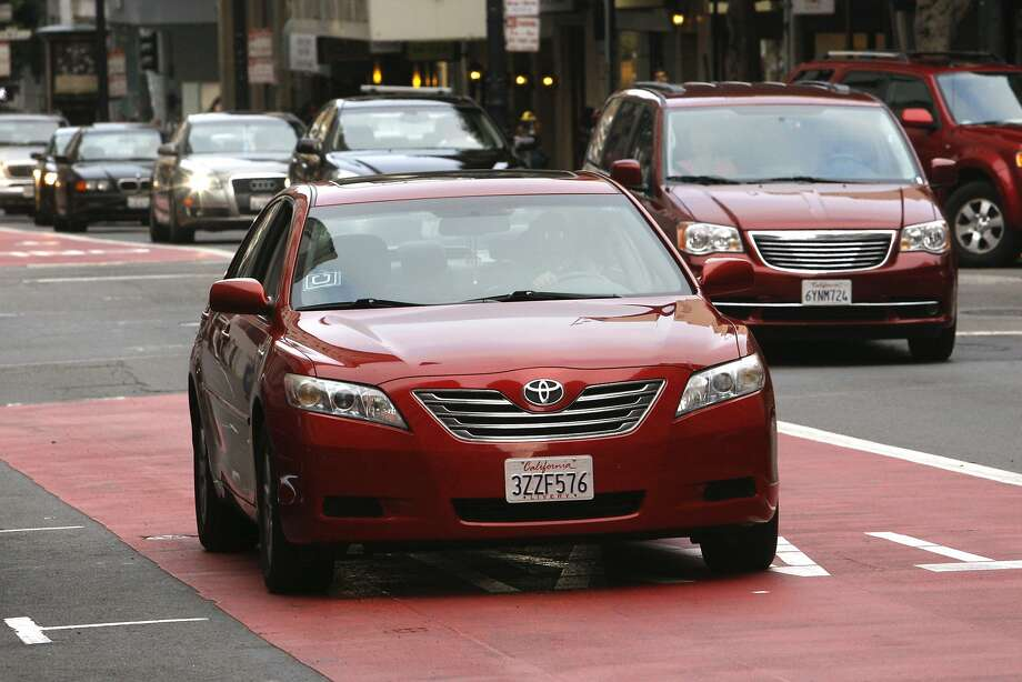 """A red sedan bearing the distinctive """"U"""" logo of the Uber ride-sharing service takes the transit lane on Geary Street in San Francisco on Friday, September 19, 2014. Photo: Terray Sylvester, The Chronicle"""
