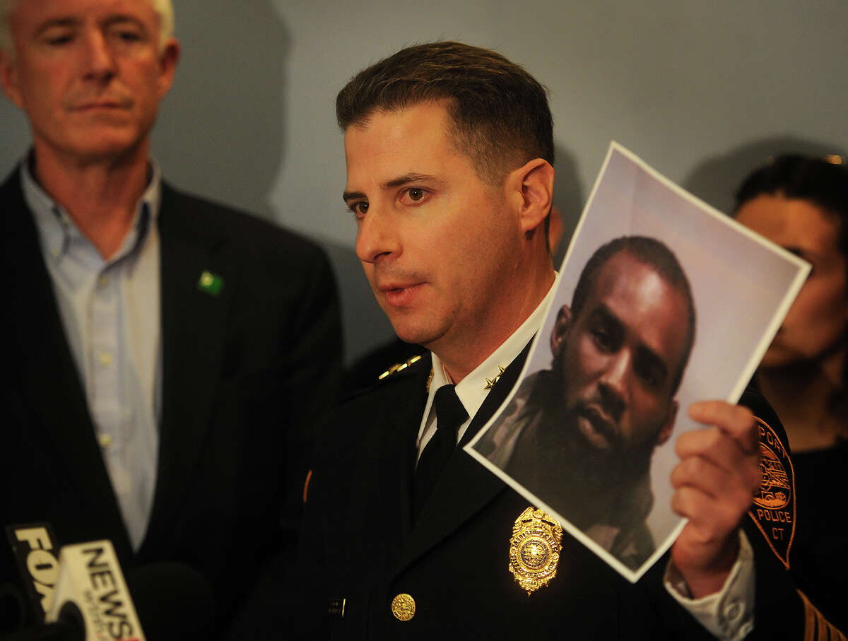 Bridgeport Assistant Police Chief James Nardozzi holds a photo of Leighton Vanderberg, 22, of New Haven, arrested for the murder of Jose Salgado at his Sapiao's Grocery Store in Bridgeport's Hollow neighborhood on Saturday, at the Margaret Morton Government Center in Bridgeport, Conn. on Wednesday, April 15, 2015. With Nardozzi is Bridgeport Mayor Bill Finch.