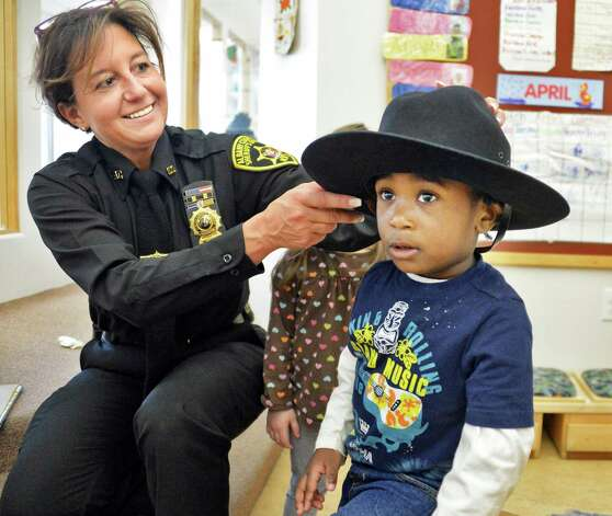 "Albany County Sheriff's investigator Tracy Mance lets NaQuien Lewis try on her uniform hat during an Club Fed Child Care Center's ""Our Family Reads!"" project event at the Leo O'Brien Federal Building Wednesday, April 15, 2015, in Albany, N.Y.  (John Carl D'Annibale / Times Union) Photo: John Carl D'Annibale / 00031441A"