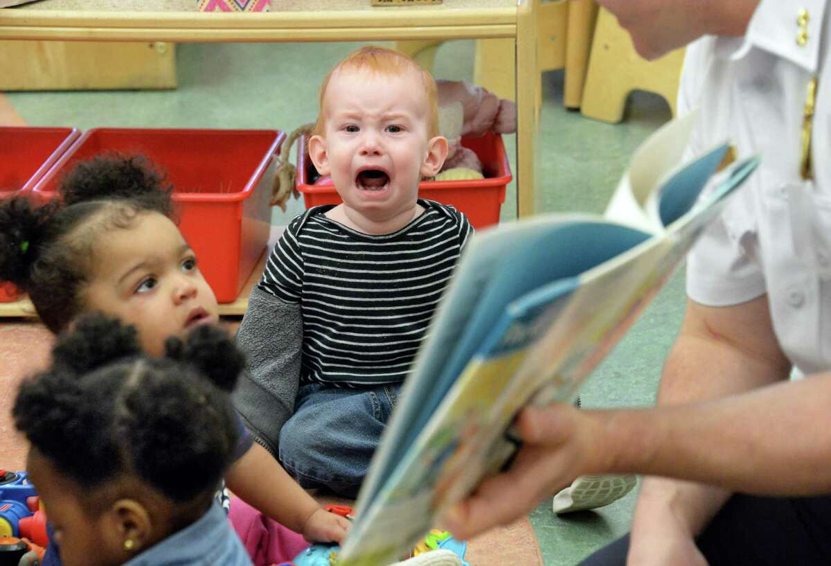 Connor Hagzan, center, begins to cry as acting Chief Brendan Cox of the Albany Police Dept. reads to toddlers during an Club Fed Child Care Center's
