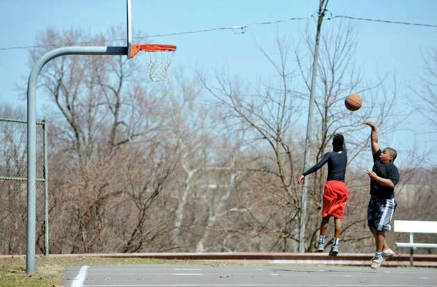 T.J. Harper, left, 13, from Troy and C.J. Nesmith, 12, from Troy play basketball at Prospect Park on Sunday, April 12, 2015, in Troy, N.Y.   (Paul Buckowski / Times Union) Photo: Albany Times Union