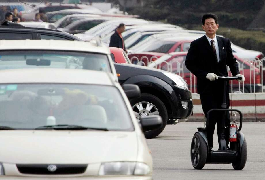A man rolls on a Segway as he practices in a parking lot in Beijing, where he sells the device. Photo: Ng Han Guan / Associated Press / AP