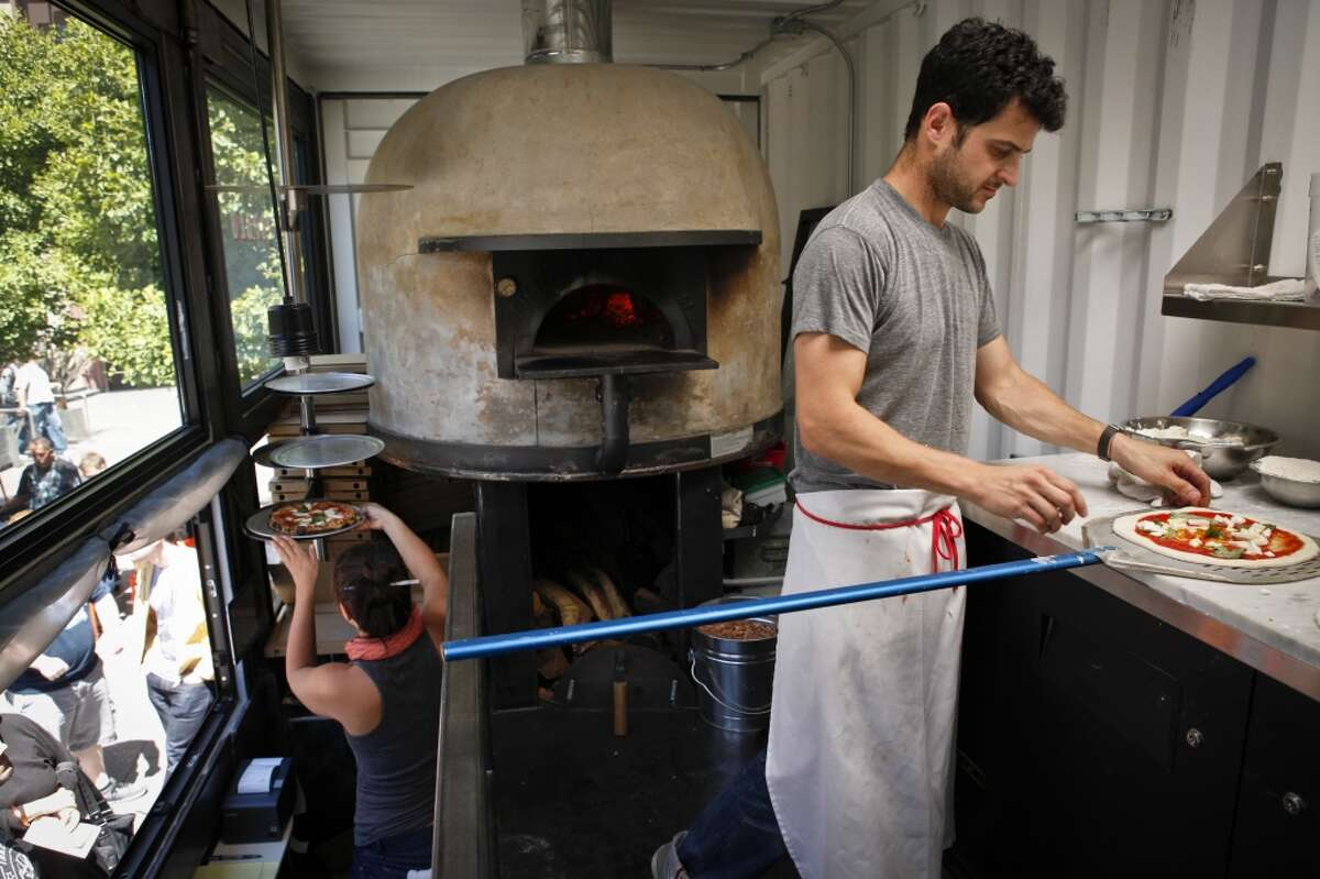 Jonathan Darsky, right, prepares to put a pizza in the oven in Del Popolo, a mobile pizzeria housed in a 25ft. shipping container, on Thursday, June 7, 2012 at Mint Plaza in San Francisco, Calif.
