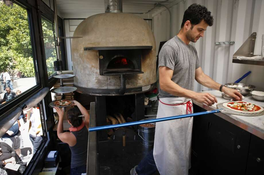 Jonathan Darsky, right, prepares to put a pizza in the oven in Del Popolo, a mobile pizzeria housed in a 25ft. shipping container, on Thursday, June 7, 2012 at Mint Plaza in San Francisco, Calif. Photo: The Chronicle