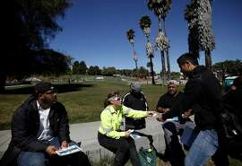 Anita Migliore of Recology, center, hands out information to members of Mission Neighborhood Services, who will be manning the new pop-up recycling and composting location at Dolores Park in San Francisco, Calif., on Wednesday, April 15, 2015.