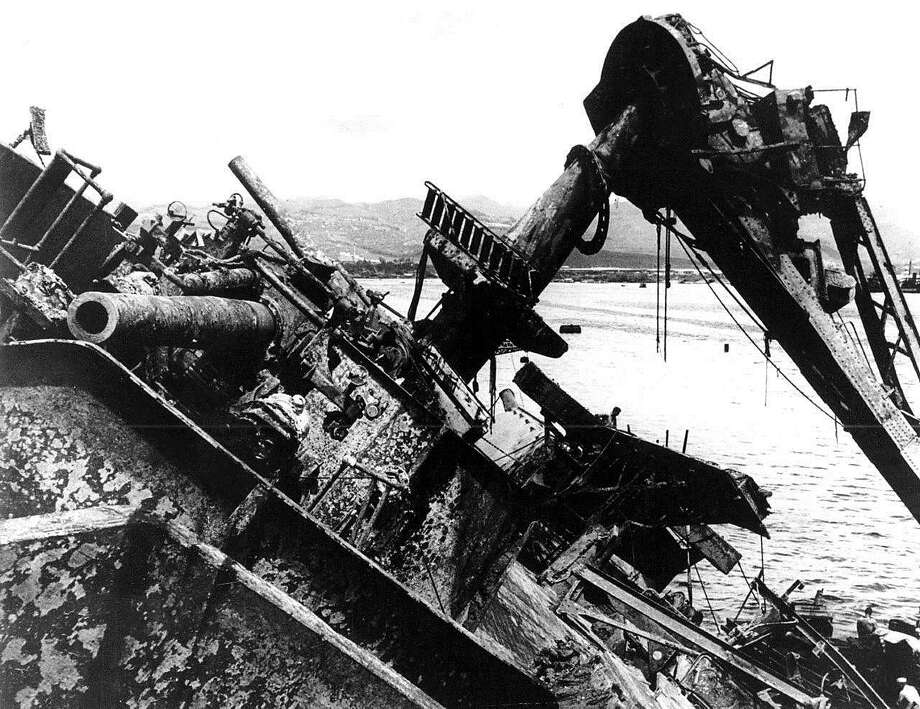 FILE - In this May 24, 1943 file photo, the deck of the capsized battleship USS Oklahoma breaks water at Pearl Harbor in Honolulu, Hawaii. The Pentagon says it will disinter and try to identify the remains of up to 388 unaccounted for sailors and Marines killed when the USS Oklahoma sank in the 1941 Japanese bombing of Pearl Harbor. (AP Photo, File) Photo: Associated Press