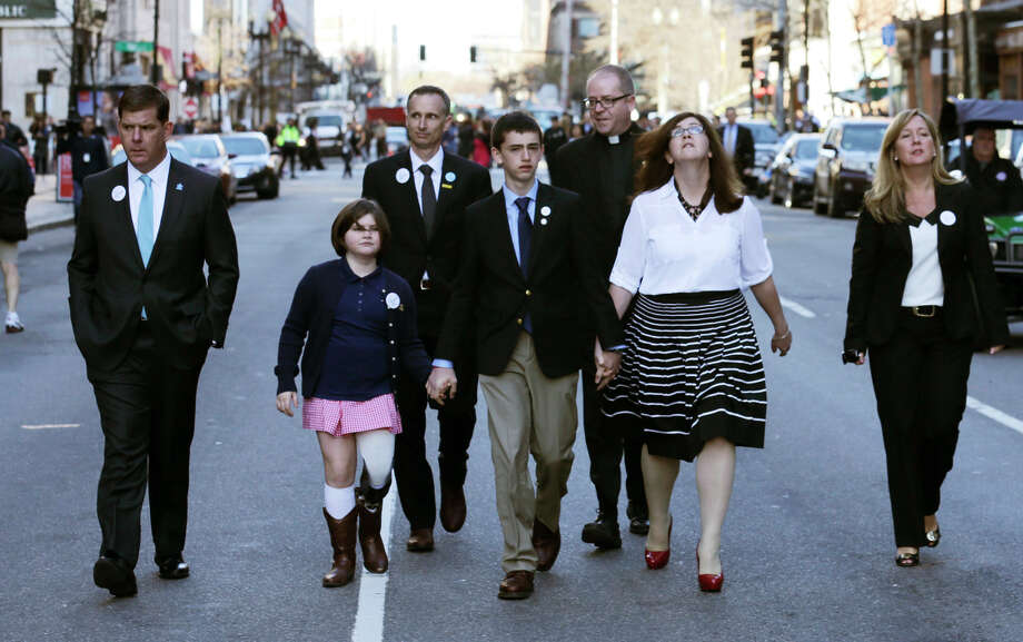 Marathon bombing survivor Jane Richard holds her brother's hand as she walks down Boylston Street with Mayor Marty Walsh (left) after the ceremony. Photo: Charles Krupa / Associated Press / AP