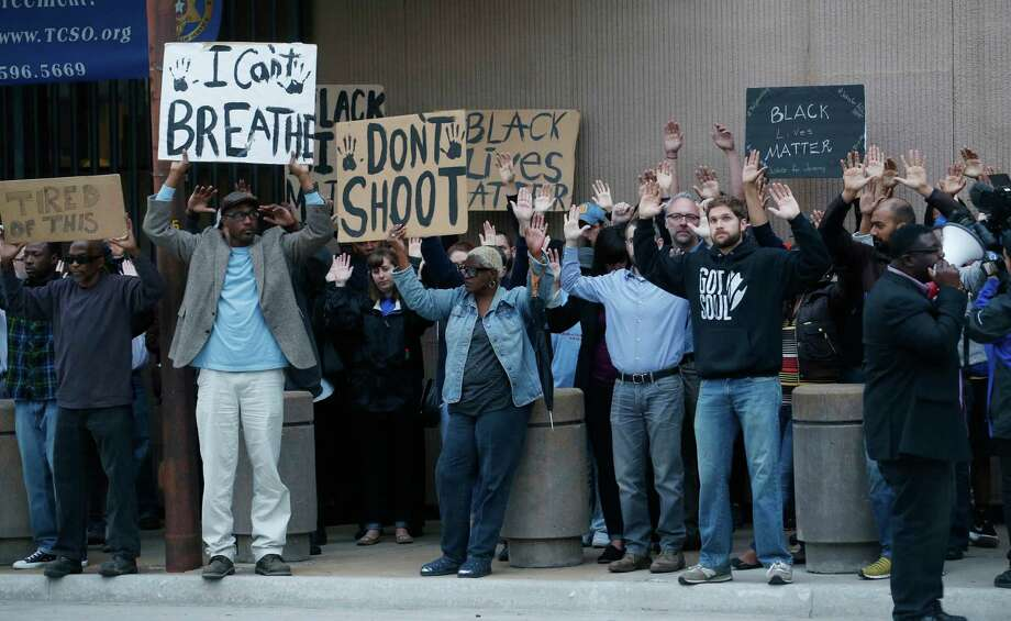 In this photo taken Tuesday, April 14, 2015, protesters, some with arms and hands raised, demonstrate outside the Tulsa County Sheriff's office in Tulsa, Okla., during a rally calling for the firing of a sheriff's deputy who can be heard in a video cursing at suspect Eric Harris as he was dying in a recent Tulsa police shooting. (James Gibbard/Tulsa World via AP) KOTV OUT; KJRH OUT; KTUL OUT; KOKI OUT; KQCW OUT; KDOR OUT; TULSA OUT; TULSA ONLINE OUT Photo: James Gibbard / Associated Press / Tulsa World