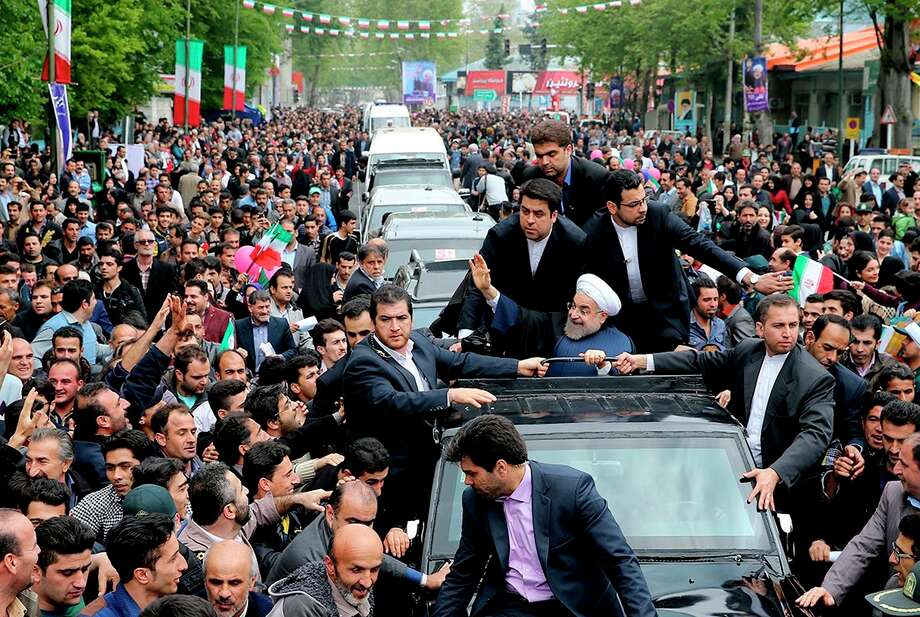 Iranian President Hassan Rouhani waves at the crowds greeting him in the northern city of Rasht. Photo: HO / AFP / Getty Images / AFP