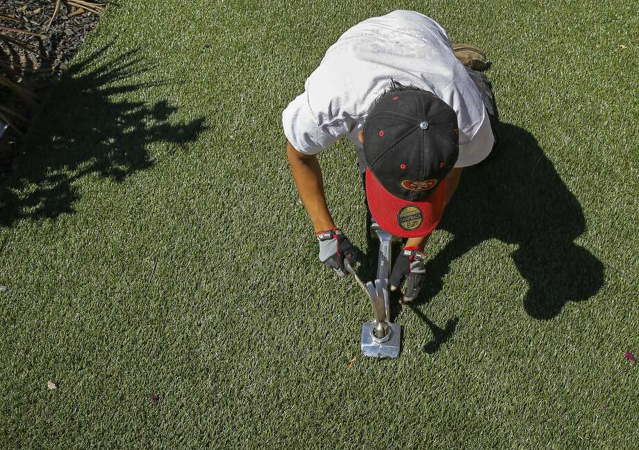 Willie Hernandez with Diamond Greens, uses a carpet tool to secure the roll the installation of an artificial lawn at a home in Walnut Creek, Calif., on Wed. April 15, 2015. With the current fourth year of drought throughout the state of California the artificial grass business is booming. Photo: Michael Macor, The Chronicle