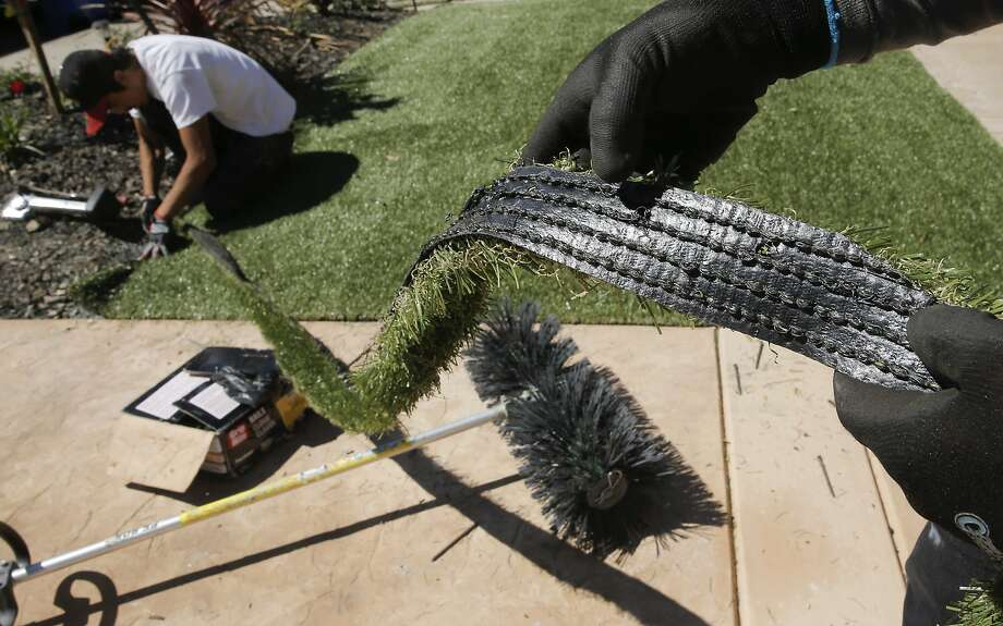 Giovanny Perez with Diamond Greens, displays a piece of the cut material being used as Willie Hernandez, (left) continues the installation of an artificial lawn at a home in Walnut Creek, Calif., on Wed. April 15, 2015. With the current fourth year of drought throughout the state of California the artificial grass business is booming. Photo: Michael Macor, The Chronicle