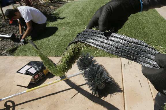 Giovanny Perez with Diamond Greens, displays a piece of the cut material being used as Willie Hernandez, (left) continues the installation of an artificial lawn at a home in Walnut Creek, Calif., on Wed. April 15, 2015. With the current fourth year of drought throughout the state of California the artificial grass business is booming.