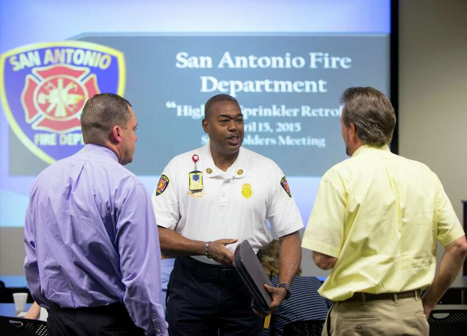 San Antonio Fire Department Chief Charles Hood, center, talks Wednesday morning April 15, 2015 to participants in the first meeting of a group put together by the fire department to discuss the feasibility of requiring residential high-rises in San Antonio without sprinklers to install them. San Anotnio is looking into this in the wake of last years' Wedgwood high rise fire in Castle Hills that killed 5 people. Photo: William Luther /San Antonio Express-News / © 2015 San Antonio Express-News