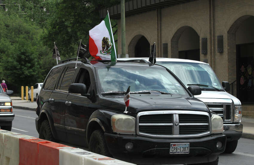 An SUV with a Mexican flag sticking out of it travels down Commerce street Wednesday April 15, 2015 in anticipation of the match between the United States and Mexico's men's national soccer teams to be held at the Alamodome.