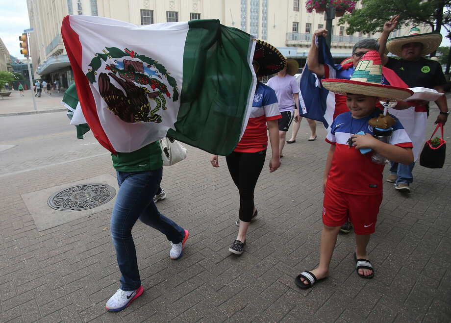 Soccer fans walk in Alamo Plaza Wednesday April 15, 2015 in anticipation of the match between the United States and Mexico's men's national soccer teams to be held at the Alamodome. Leading the charge with the Mexican flag (left) is Arlette Barajas,11, who was with her dad Julio Barajas. The family came from McAllen to see the soccer match. Photo: John Davenport, SAEN / ©San Antonio Express-News/John Davenport