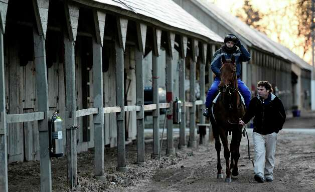 Trainer Kerry Metivier leads the first horse of the season  Oliver Bush with exercise rider Marcos Acosta aboard to the Oklahoma Training Track on opening day Wednesday April 15, 2015 in Saratoga Springs, N.Y.      (Skip Dickstein/Times Union) Photo: SKIP DICKSTEIN / 00031454A