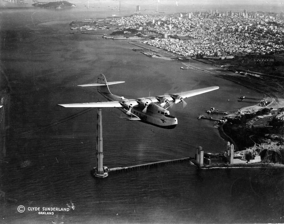The famous China Clipper shown soaring over the Golden Gate Bridge, bound to Hawaii and the Philippines It was the inaugural flight of the Pan American Airways commercial flying service.