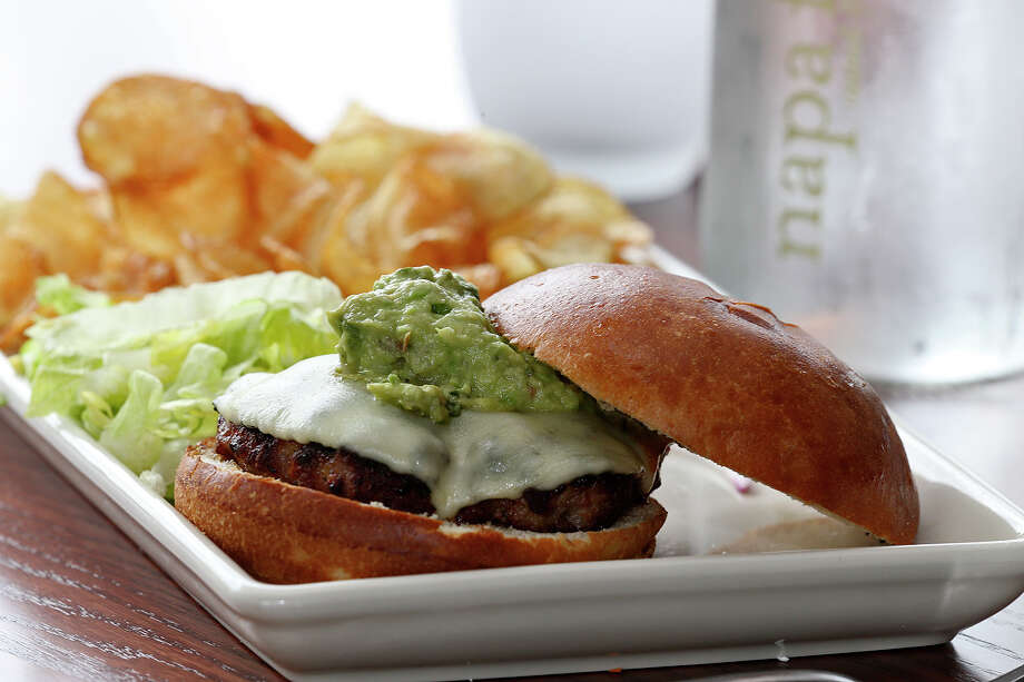 The Fresno Burger is made with a wood-fired, hand formed pork patty topped with melted provolone and housemade guacamole at Napa Flats. Homemade chips accompany the burgers. Photo: Jerry Lara /San Antonio Express-News / © 2015 San Antonio Express-News