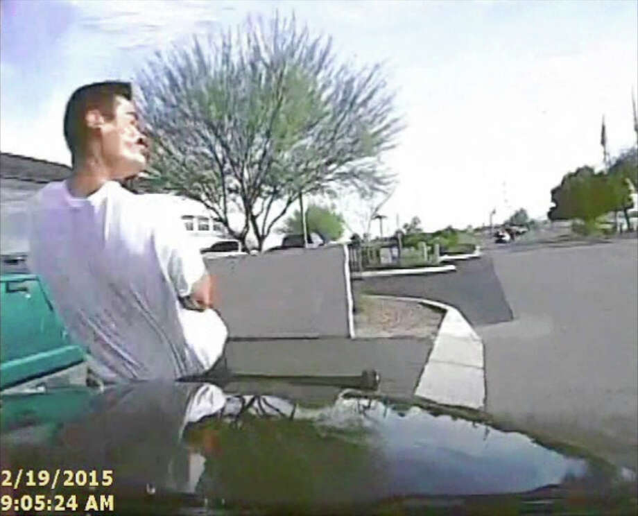This image from a dash cam video shows the police car hitting Mario Valencia, who was walking along a street, armed with a rifle. Photo: Associated Press / Marana Police Department