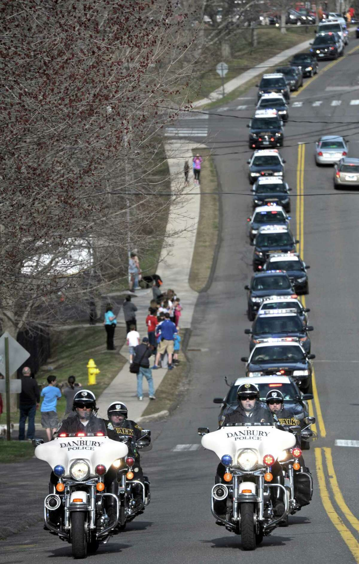 Zeus, a german shepherd who worked for the Ridgefield Police Department was honored with a final ride before being euthanized because of a severe degenerative hip disorder on Wednesday afternoon, April 15, 2015, in Ridgefield, Conn. The procession makes its way down Governor Street on its way to Main Street followed by the Ridgefield Veterinary Hospital.