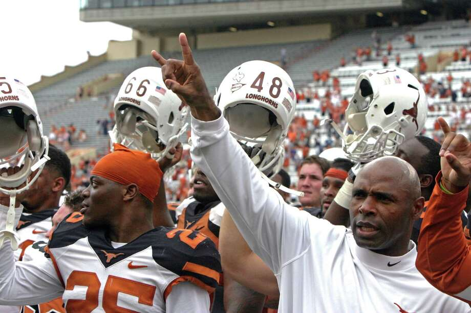 "Texas coach Charlie Strong gives the ""Hook 'em Horns"" sign while his players raise their helmets after the Orange and White spring game in 2014 in Austin. Photo: Michael Thomas /Associated Press / FR65778 AP"