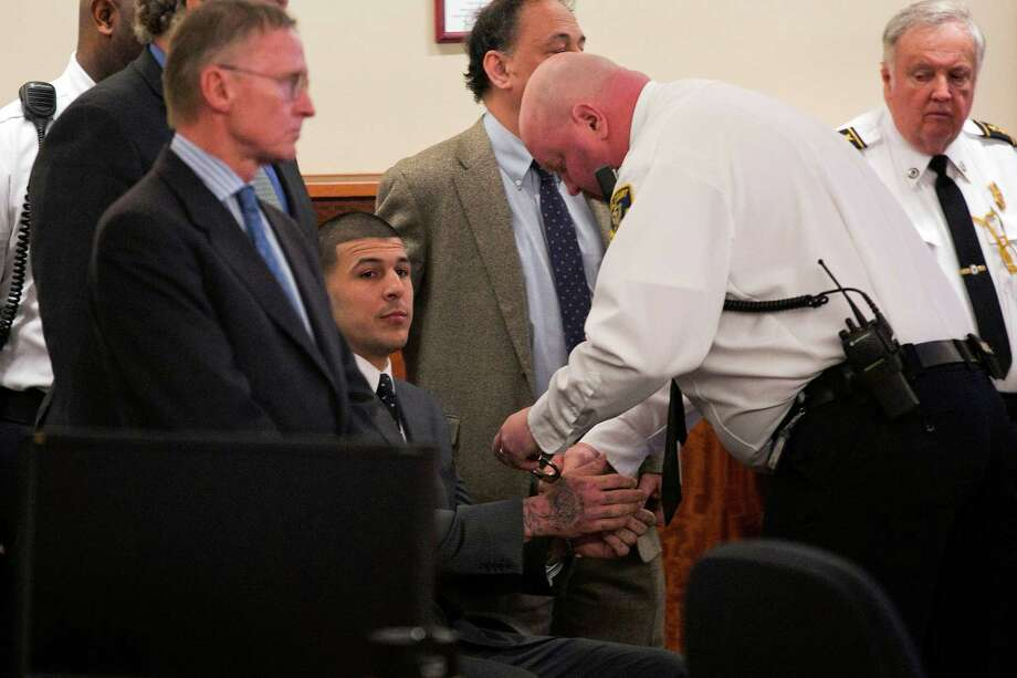 An officer puts handcuffs on former Patriots football player Aaron Hernandez after he was read the guilty verdict Wednesday. Photo: Dominick Reuter / Associated Press / Pool Reuters