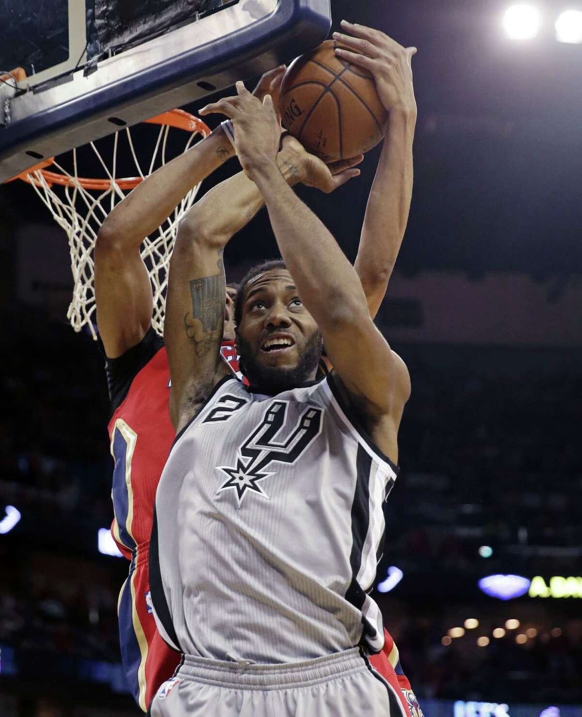 San Antonio Spurs forward Kawhi Leonard (2) battles for a rebound with New Orleans Pelicans forward Anthony Davis in the first half of an NBA basketball game in New Orleans, Wednesday, April 15, 2015.