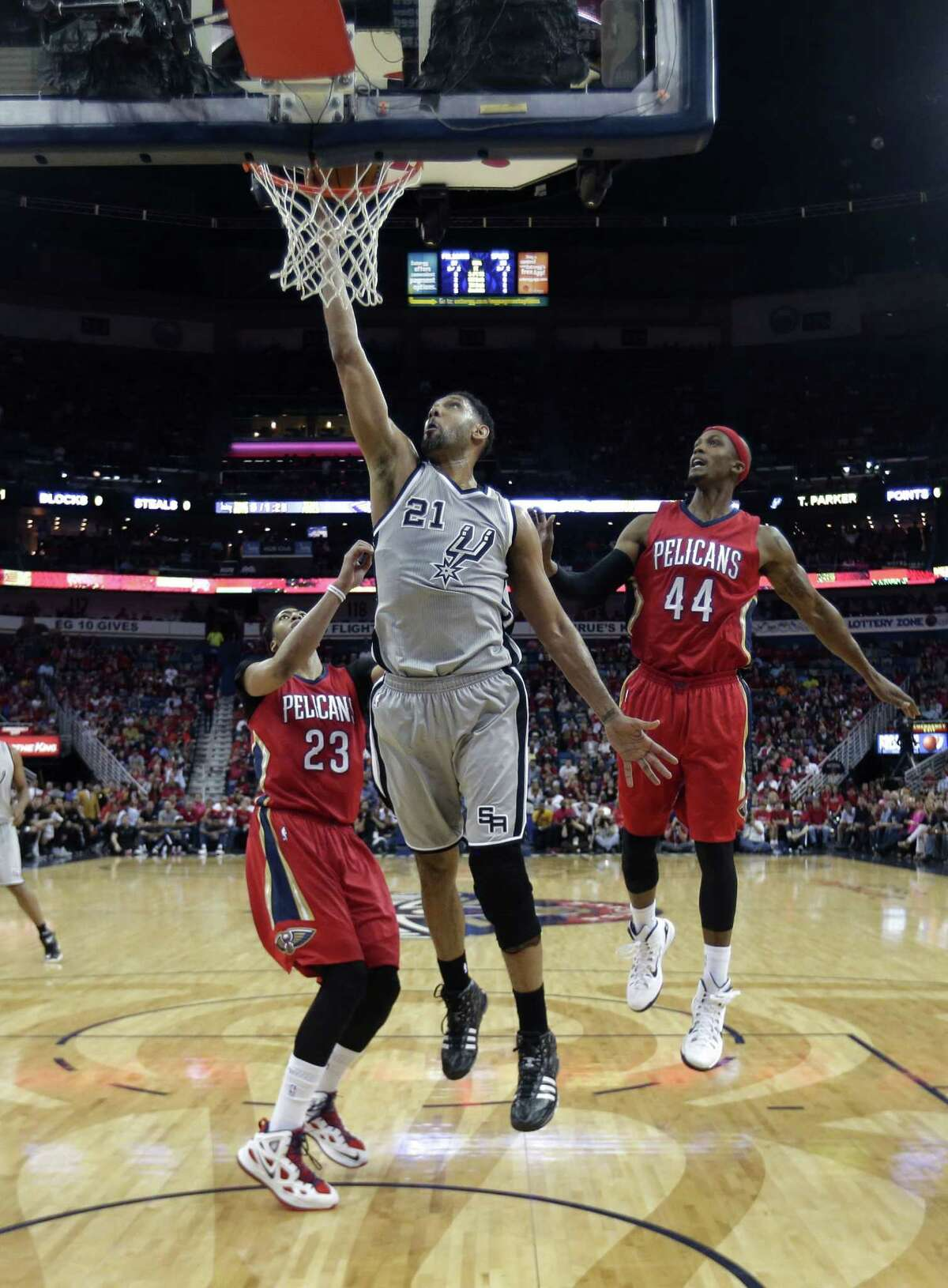 San Antonio Spurs forward Tim Duncan (21) goes to the basket in front of New Orleans Pelicans forward Anthony Davis (23) and forward Dante Cunningham (44) in the first half of an NBA basketball game in New Orleans, Wednesday, April 15, 2015.