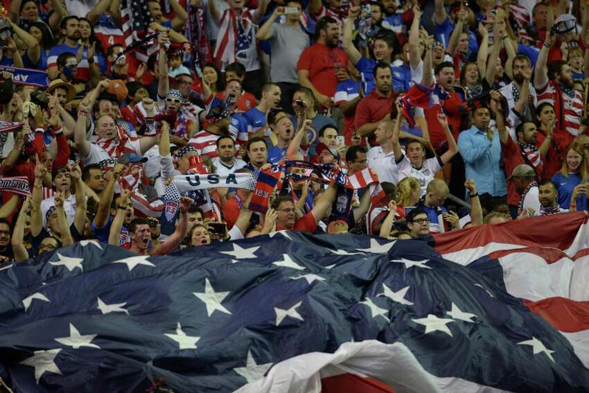 USA fans cheer as a flag is unfurled before the international friendly match against Mexico at the Alamodome on Wednesday, April 15, 2015.