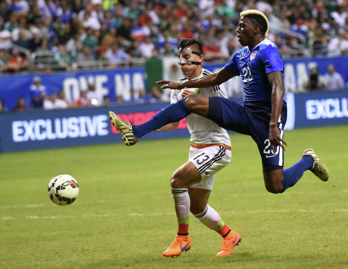 Gyasi Zardes of the USA kicks a shot on goal as Cirilo Saucedo of Mexico defends during an international friendly match at the Alamodome on Wednesday, April 15, 2015.