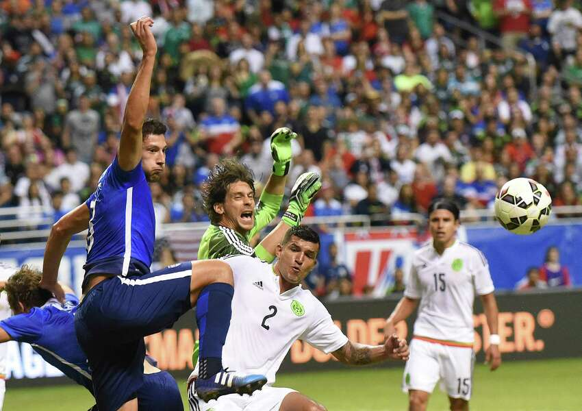 Omar Gonzalez of the USA left, battles Mexico's Francisco Rodriguez (2) near the goal during an international friendly match at the Alamodome on Wednesday, April 15, 2015.