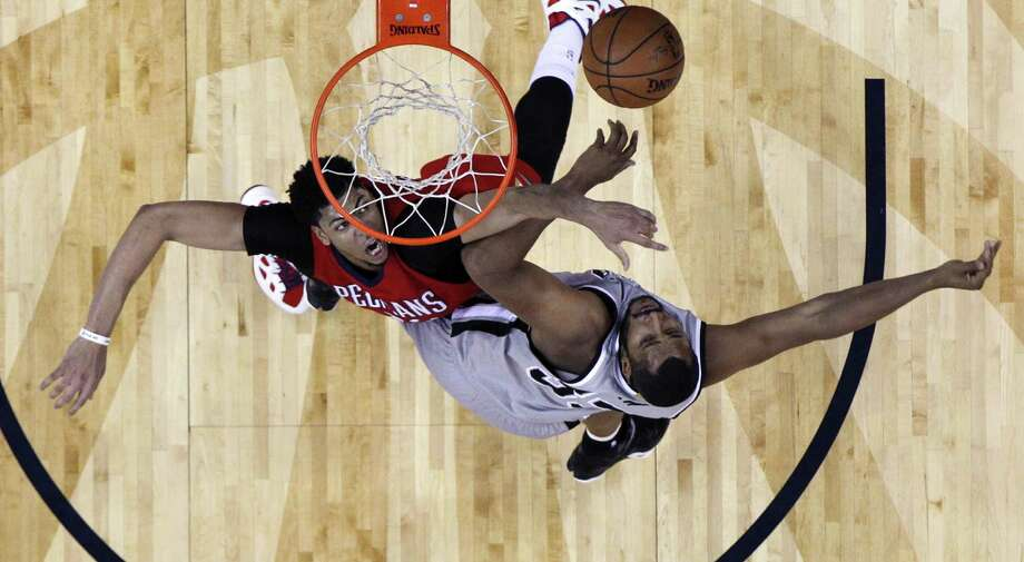 New Orleans Pelicans forward Anthony Davis, top left, and San Antonio Spurs center Boris Diaw (33) battle under the basket in the first half of an NBA basketball game in New Orleans, Wednesday, April 15, 2015. Photo: Gerald Herbert, AP / AP