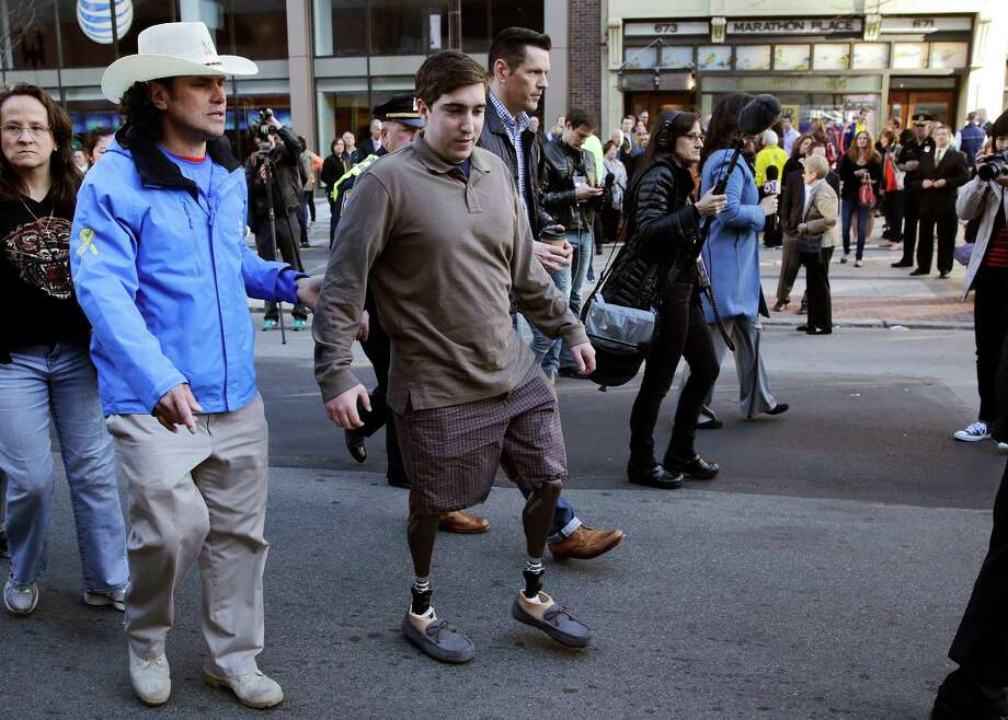 Boston Marathon survivor Jeff Bauman passes one of two blast sites with Carlos Arredondo (left), who helped save his life, near the finish line of the Boston Marathon. The city marked the anniversary with a subdued remembrance. Photo: Charles Krupa / Associated Press / AP