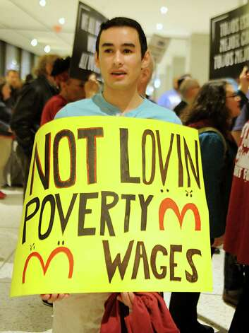 Daniel Fitzsimmons, 18, of Bethlehem holds a sign as fast food workers and other rally in support of a $15 per hour minimum wage at the Empire State Plaza on Wednesday, April 15, 2015 in Albany, N.Y. (Lori Van Buren / Times Union) Photo: Lori Van Buren / 00031444A