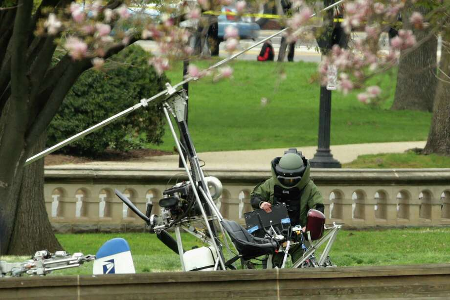 A member of the Capitol Police bomb squad works to check and secure a gyrocopter that landed on the West Lawn of the U.S. Capitol. Photo: Chip Somodevilla / Getty Images / 2015 Getty Images