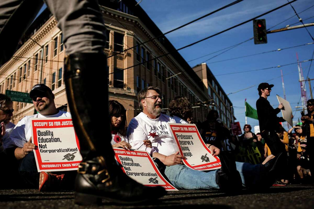 Twenty-one protesters willing are put under arrest during a rally as part of the national mobilization in the movement against poverty-wage jobs, photographed Wednesday, April 15, 2015, in Seattle, Washington. Uber drivers, retail workers and adjunct professors joined fast food workers to march side by side.