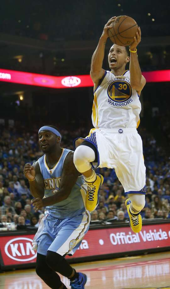 Golden State Warriors' Stephen Curry scores against Denver Nuggets' Ty Lawson during NBA game at Oracle Arena in Oakland, Calif., on Wednesday, April 15, 2015. Photo: Scott Strazzante, The Chronicle