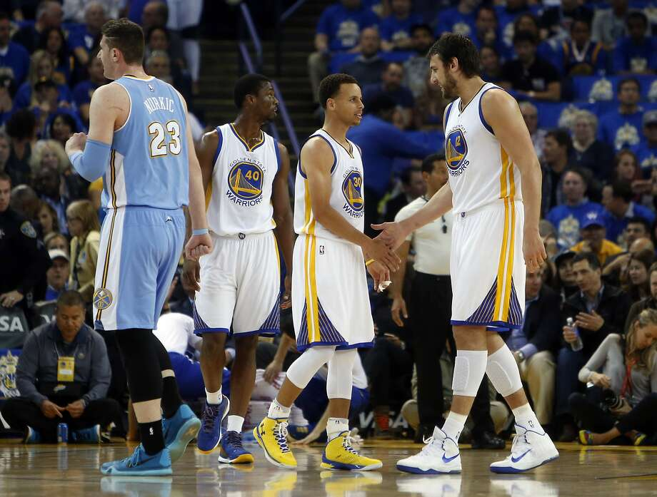 Golden State Warriors' Stephen Curry and Andrew Bogut slap hands in 1st quarter against Denver Nuggets during NBA game at Oracle Arena in Oakland, Calif., on Wednesday, April 15, 2015. Photo: Scott Strazzante, The Chronicle