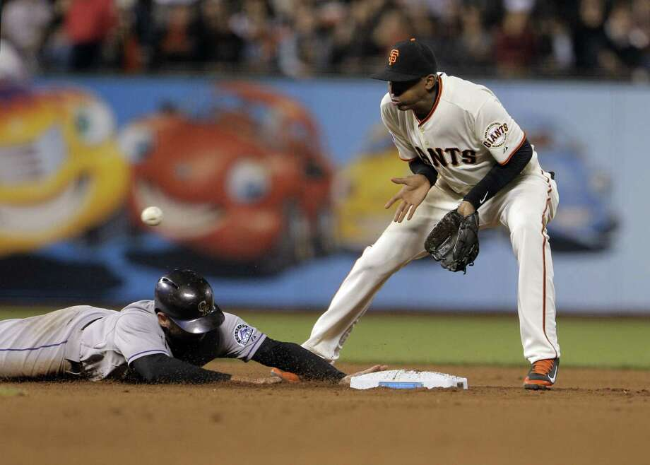 Joaquin Arias (13) waits for the ball on a pick off attempt in the as Michael McKenry (8) dives back safely. The San Francisco Giants played the Colorado Rockies at AT&T Park in San Francisco, Calif., on  Wednesday, April 15, 2015. Photo: Carlos Avila Gonzalez / The Chronicle / ONLINE_YES