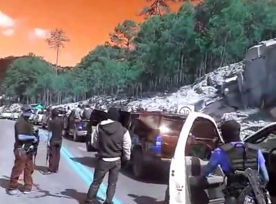 A video posted to YouTube on April 8, 2015, by online tabloid La Polaka shows several masked men with assault rifles sitting in and standing around pickup trucks stopped on a mountain road in Southwestern Chihuahua. The Chihuahua state attorney general's office told the El Paso Times that the footage was filmed before a September battle between two rival groups near the town of Tonachí, where Mexican authorities found 11 men dead and four torched vehicles. Photo: Screenshot Via YouTube