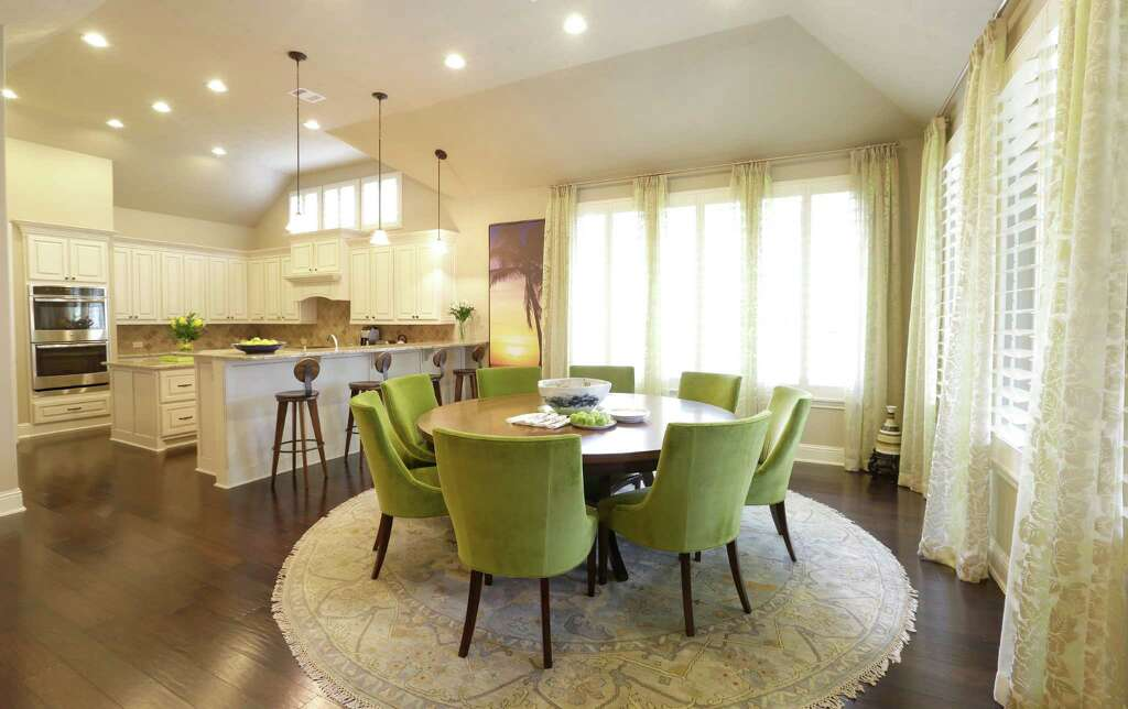 Big Windows Light An Open Dining Area, Where Eight Chartreuse Chairs  Surround A Round Wooden