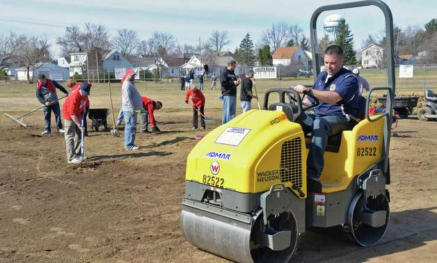 Cohoes Little League president Mike Smith drives a roller as volunteers of the '4 in 24' Youth Field Renovation Project work at Berkley Park Thursday April 16, 2015, in Cohoes, NY.  (John Carl D'Annibale / Times Union) Photo: John Carl D'Annibale / 00031436A