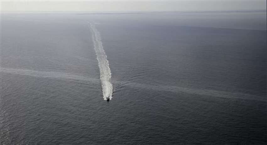 In this March 31, 2015 photo, a supply vessel crosses an oil sheen drifting from the site of the former Taylor Energy oil rig in the Gulf of Mexico, off the coast of Louisiana. The New Orleans-based company has downplayed the leak's environmental impact, likening it to scores of minor spills and natural seeps that the Gulf routinely absorbs. (AP Photo/Gerald Herbert)