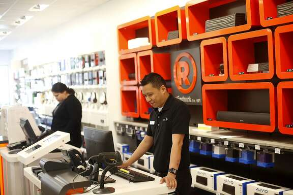 Jimmy Yeo, a Sprint lead retail associate, and Rebecca Sanchez, a Radio Shack sales associate, work at a co-branded Sprint-Radio Shack store in the Castro in San Francisco, Calif., on Thursday, April 16, 2015.  Sprint recently made a deal with struggling consumer electronics retailer Radio Shack to co-brand the latter's stores.