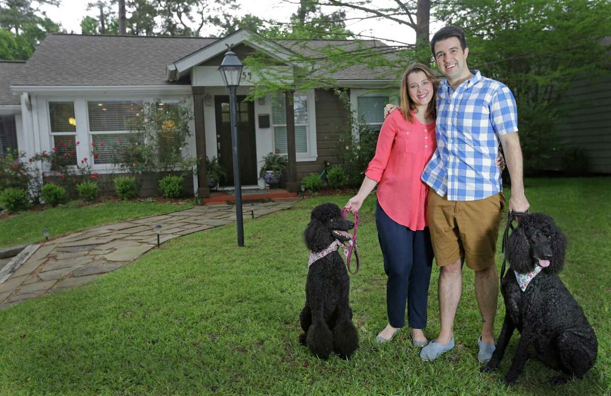 Creighton and Michelle Welch pose with their standard poodles Penny, left, and Paco, outside their home in Garden Oaks Sunday, April 12, 2015, in Houston.