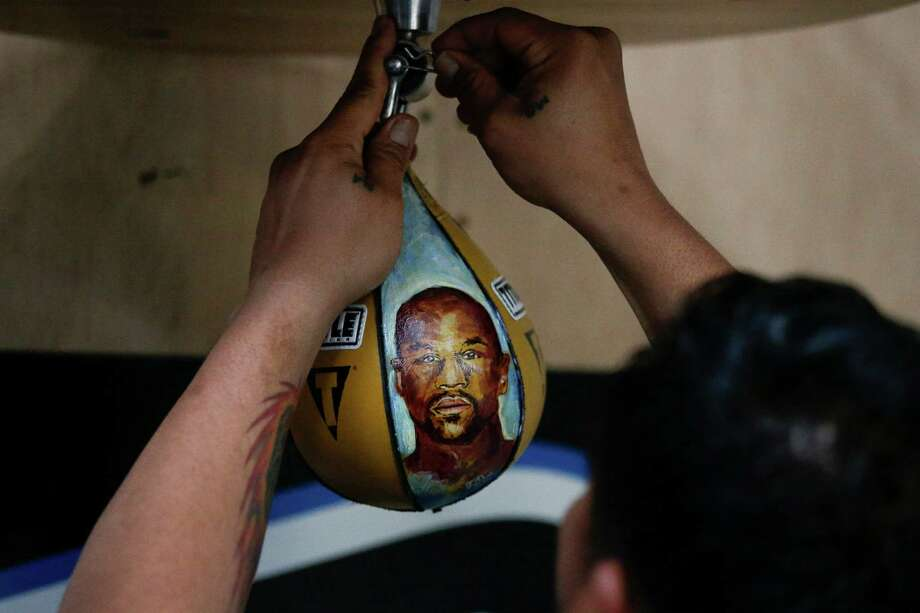 A member of the Manny Pacquiao's training camp hangs a speed bag showing an image of Floyd Mayweather Jr. during a workout on April 13, 2015, in Los Angeles. The two are scheduled to fight in a welterweight boxing match in Las Vegas on May 2. Photo: Jae C. Hong /Associated Press / AP