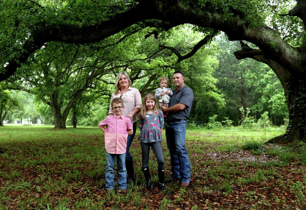 """Deuce Robison, of Erbauer LLC, construction services, with wife Buffy and children Lott, six, Dossholly, nine, and Briar, 21-months, at their home Saturday, April 11, 2015, in Crosby, Texas. The Robisons purchased a 100-year-old former dairy farm home currently being refurbished. """"This is the place I wanted for a long time,"""" said Deuce, """"Since I was a child."""""""