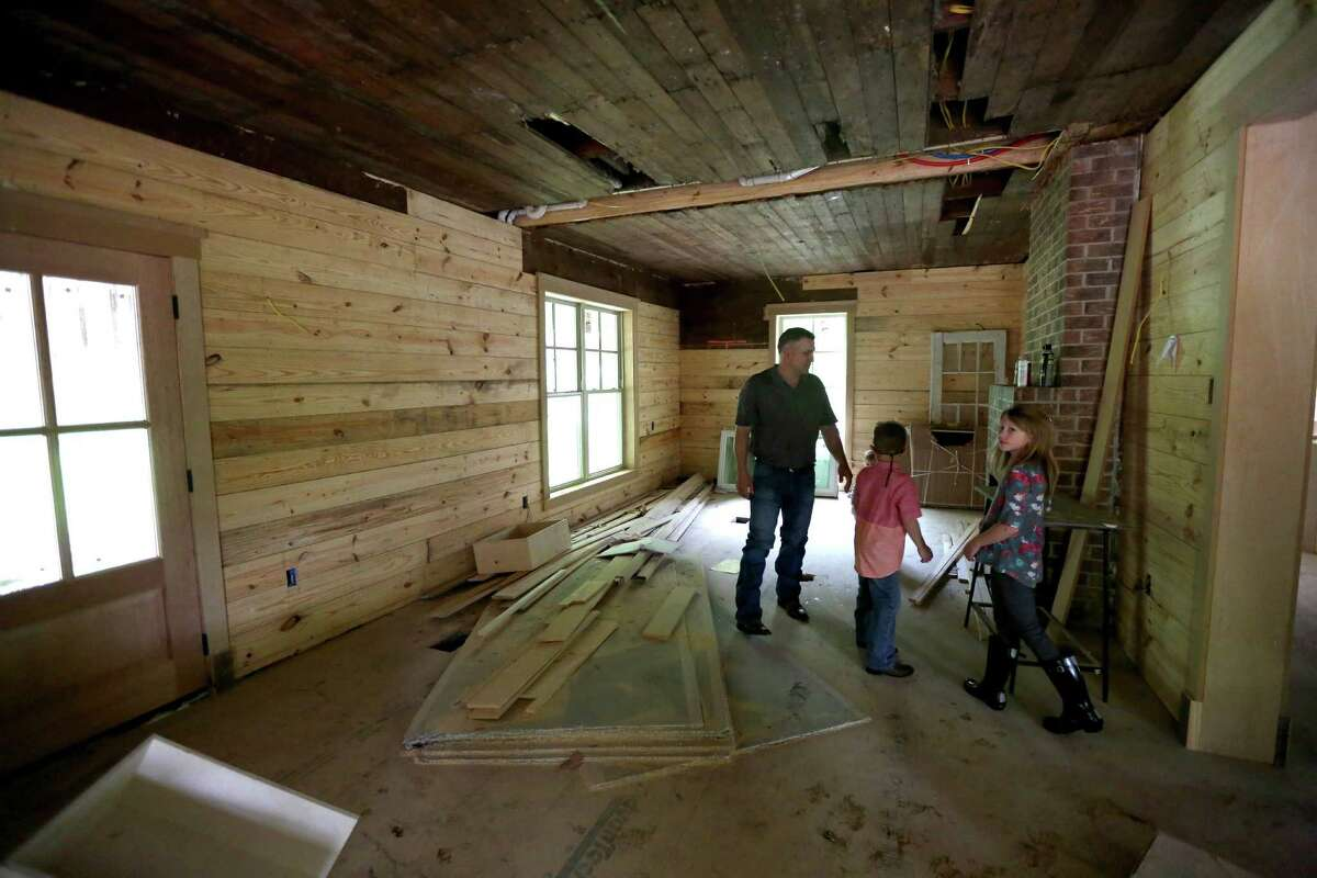 """Deuce Robison, of Erbauer LLC, construction services, with children Lott, six, and Dossholly, nine, at their home Saturday, April 11, 2015, in Crosby, Texas. The Robisons purchased the 100-year-old former dairy farm home currently being refurbished. """"This is the place I wanted for a long time,"""" said Deuce, """"Since I was a child."""""""