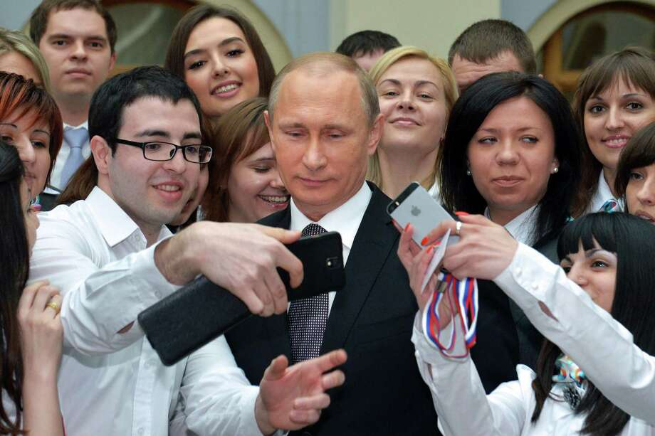 Russian President Vladimir Putin takes pictures with admirers after his annual televised phone-in with the nation in central Moscow. Photo: ALEXEI DRUZHININ / AFP / Getty Images / AFP