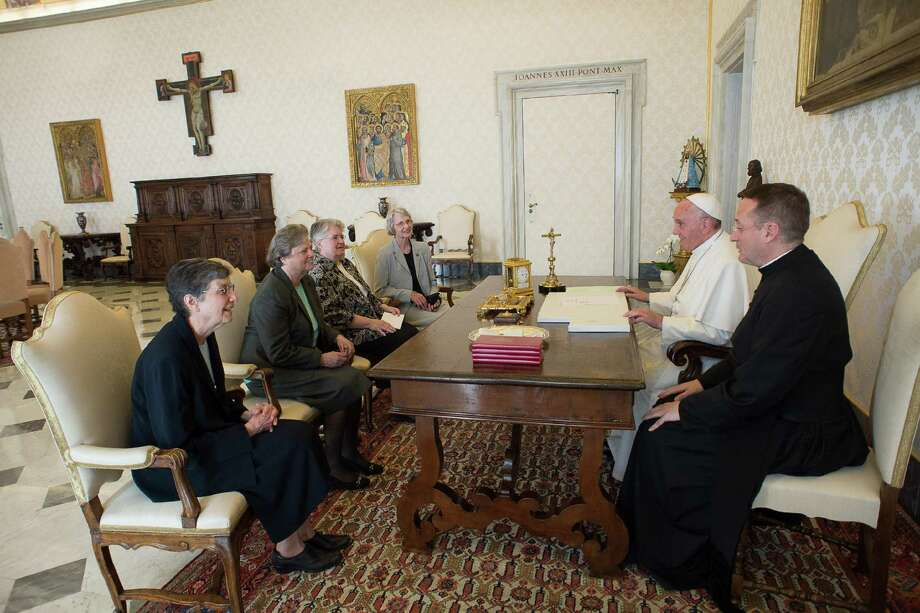 Pope Francis (in white robes) talks with a delegation of the Leadership Conference of Women Religious during an audience in the pontiff's studio at the Vatican. The Vatican has announced the unexpected conclusion of a controversial overhaul of the main umbrella group of U.S. nuns in a major shift in tone and treatment of American nuns under the social justice-minded Pope Francis. Photo: L'Osservatore Romano / Associated Press / L'Osservatore Romano Pool
